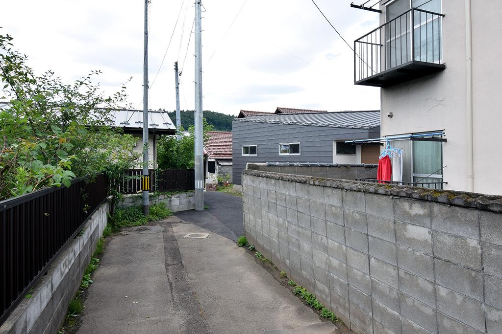 路地(法42条3項道路)の奥に建つ平屋の住宅の設計事例。アプローチ外観 バス通りから幅2.7mの細い路地を進むと徐々に姿を現す路地奥の平屋の住宅。