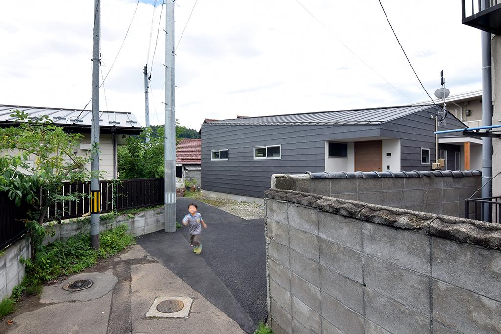 路地(法42条3項道路)の奥に建つ平屋の住宅の設計事例。路地の奥に徐々に姿を現す。