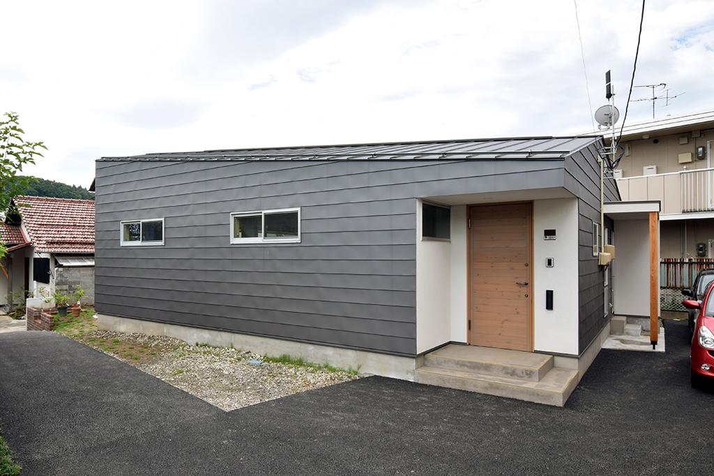 路地(法42条3項道路)の奥に建つ平屋の住宅の設計事例。アプローチ側外観。圧迫感を生まないように、玄関部分の軒高を低く設定。見る方向によって片流れ屋根に見えたり切妻屋根に見えたり、印象が変わります。 玄関ドアは木製。ポーチ土間は土たたき風左官材料。