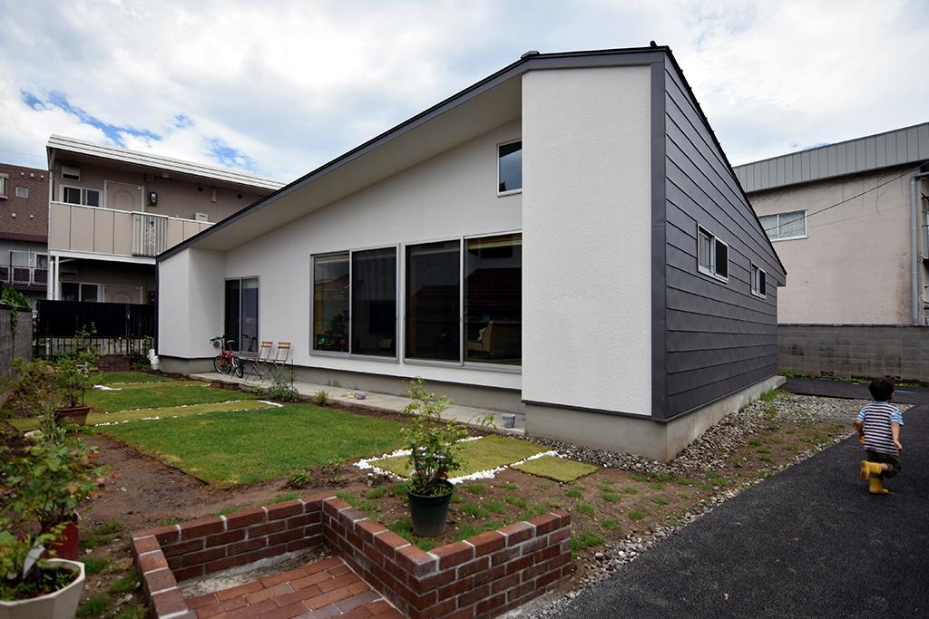 路地(法42条3項道路)の奥に建つ平屋の住宅の設計事例。庭側外観。サッシの左右に突き出したボリュームは防火壁の役割を持つとともに、近隣からの視線をコントロールもしています。