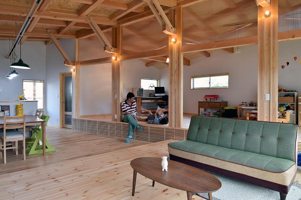 路地(法42条3項道路)の奥に建つ平屋の住宅の設計事例。リビングからダイニングを振り返る。一段高くなった多目的室は将来的には子ども部屋や書斎として仕切っての利用も想定。段差は腰を掛けるのにちょうどよい高さ。